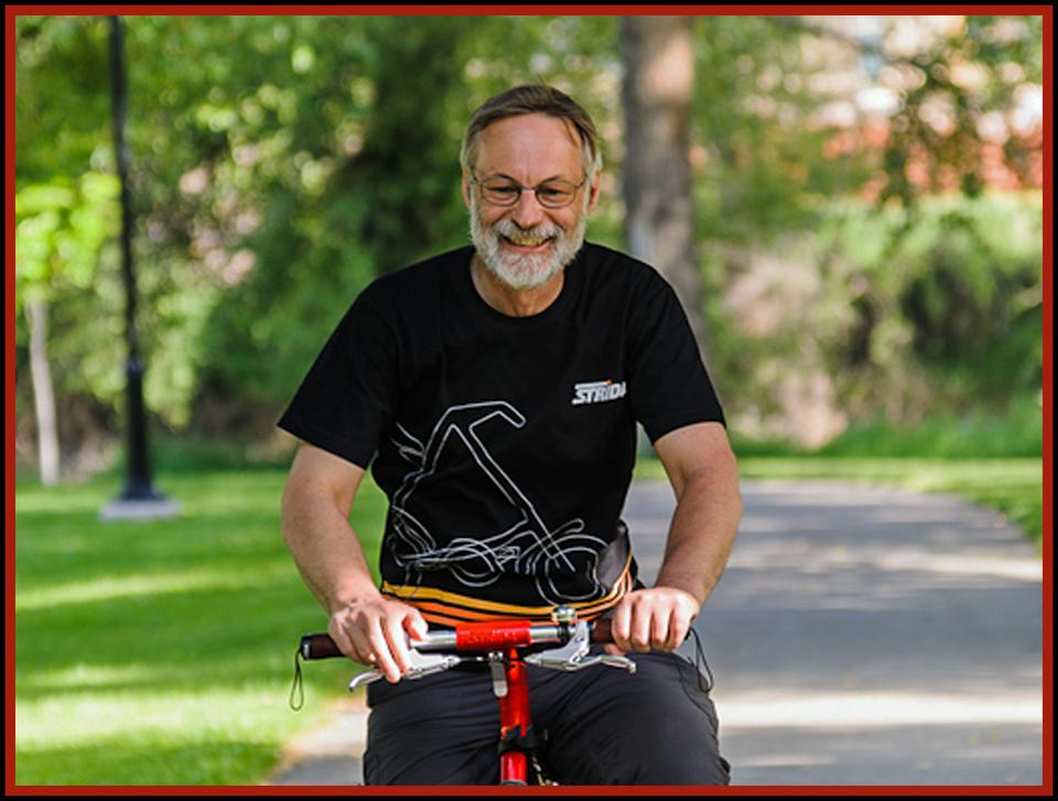 Bill Wilby riding a red Strida EVO on a bike path